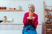 Módní ženy v barevných šatech sedí a drží desku palačinek v kuchyni