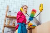 ernsthafte Hausfrau in bunten Kleidern mit Abstauben Pinsel reden auf Retro-Telefon in der Küche