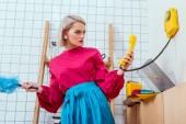 Fotografie verwirrt Hausfrau in bunten Kleidern Blick auf Retro-Telefon in der Küche