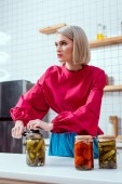 selective focus of beautiful stylish housewife sealing jar of pickled cucumbers in kitchen