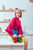 selektiver Fokus der schönen modischen Hausfrau, die auf der Küchentheke sitzt, mit eingelegtem Gemüse in der Küche