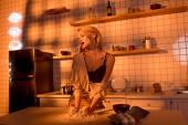 Fotografie elegantní hospodyně s moukou na pult vaření a kouří v kuchyni s oranžové světlo