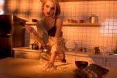 Fotografie Schöne Hausfrau qualmender Zigarette beim Kochen in der Küche mit orangefarbenen Licht