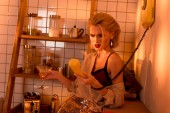 frustrated woman holding retro telephone and cocktail glass in kitchen with orange light