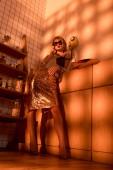 Fotografia bella donna elegante in occhiali da sole comunica sul retro telefono in cucina con la luce arancione