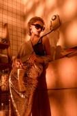 elegant woman in sunglasses holding retro telephone in kitchen with orange light