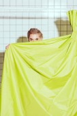 Photo young woman hiding behind green curtain with copy space in shower