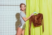 Photo beautiful woman holding bronze top on hanger in shower with green curtain