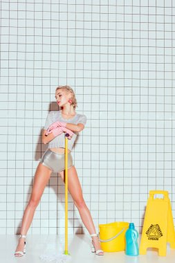 young housewife holding mop and posing with cleaning equipment and white tile on background