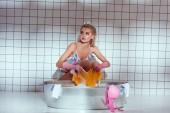 schöne Hausfrau in Gummihandschuhen Wäsche waschen im Badezimmer