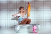 Unzufriedene Hausfrau in Gummihandschuhen wäscht Wäsche im Badezimmer