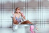 Fotografie Schöne Hausfrau in Gummihandschuhe Rauchen während der Wäsche im Bad mit Textfreiraum
