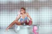 Fotografie beautiful housewife in rubber gloves looking at camera and smoking while washing clothes in bathroom