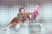Photo confused young woman in wash tub holding bra while bathing