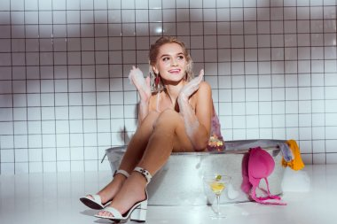 beautiful smiling young woman sitting in wash tub and gesturing with hands in bathroom
