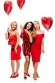 krásné usměvavé mnohonárodnostní dívky s balónky ve tvaru srdce a sklenky na sekt izolované na bílém