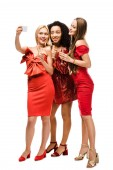 Fotografie beautiful multiethnic girls in red dresses with champagne glasses taking selfie on smartphone isolated on white