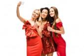Fotografie mnohonárodnostní krásky v červených šatech s sklenky na sekt s selfie na smartphone izolované na bílém