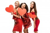 beautiful happy multiethnic girls holding cardboard hearts and posing isolated on white