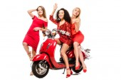 Photo beautiful happy multiethnic girls in red dresses posing on motor scooter isolated on white
