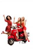 Fotografie schöne multiethnischen Mädchen in roten Kleidern auf Motorroller jubeln mit Sektgläsern isoliert auf weiss