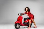 Fényképek szép afro-amerikai lány piros ruhában pózol a robogó a szürke háttér