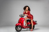 Fotografie beautiful smiling african american girl in red dress posing with motor scooter on grey background
