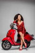 beautiful african american girl in red dress sitting on motor scooter and posing on grey background
