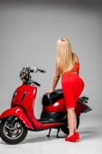 Photo back view of girl in red dress posing with motor scooter on grey background