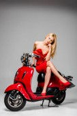 Fotografie beautiful pensive girl in red dress posing while sitting on motor scooter on grey background