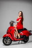 attractive girl in red dress sitting on motor scooter and looking at camera on grey background