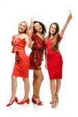 schöne glückliche multiethnischen Mädchen in roten Kleidern jubeln mit Sektgläsern isoliert auf weiss