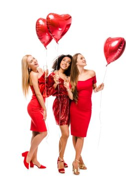 beautiful happy multiethnic girls with heart shaped balloons and champagne glasses isolated on white