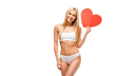 beautiful smiling girl in underwear holding heart shaped card isolated on white