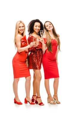 beautiful smiling multiethnic girls in red dresses looking at camera and posing with champagne glasses isolated on white