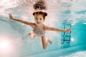 adorable kid swimming underwater in blue water in swimming pool