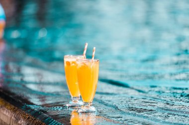 two orange cocktails glasses with straws standing at poolside