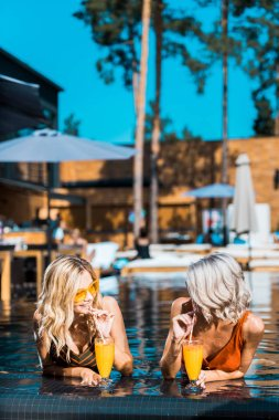 stylish women relaxing in swimming pool with cocktails
