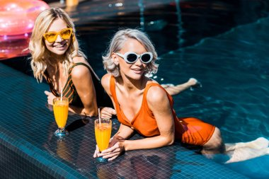 stylish blonde young women relaxing in swimming pool with cocktails