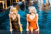 Fotografie stylish girls in swimsuits relaxing in swimming pool with cocktails