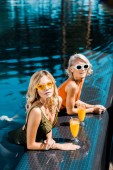 Fotografia blonde pin up ragazze con bicchieri di succo darancia rilassante in piscina