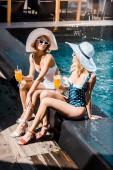 schöne lächelnde Frauen sitzen am Pool mit Cocktails