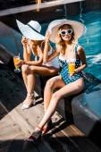attraktive glückliche Mädchen in Badeanzügen Entspannung am Pool mit cocktails
