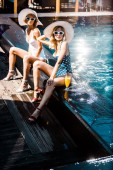 Fotografie Nádherná sponka se dívky sedí u bazénu se sklenkou koktejlu