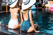 Fotografie pin up girls in swimsuits and hats sitting at poolside