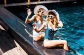 dívky v sluneční brýle a klobouky mává v bazénu