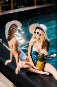 Fotografie blond pin se ženy představují s ananasem v plaveckém bazénu