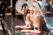 krásné dívky v sluneční brýle a klobouky pózuje v bazénu