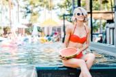 Fotografia bella donna in costume da bagno alla moda con anguria succosa a bordo piscina