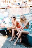krásný usměvavý pin se dívky v sluneční brýle a plavky drží bubliny při posezení u bazénu